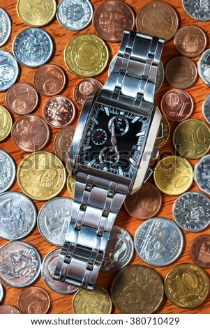 Men's wrist watch on metal coins as in time is money concept - stock photo