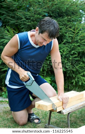 Men sawing wood outdoors