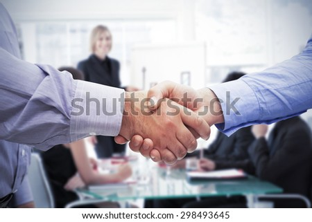 Men shaking hands against businesswoman reporting to sales in a seminar - stock photo