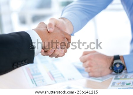 Men shaking hands. Confident businessman shaking hands with each other. Close-up view of the hands of a businessman in the office of the table in the formal wear. - stock photo