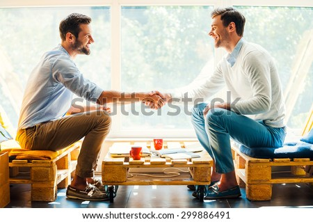 Men shaking hands. Side view of two happy young men shaking hands while sitting in front of the window - stock photo