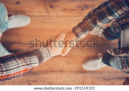 Men shaking hands. Top view of two men shaking hands while standing on the wooden floor - stock photo