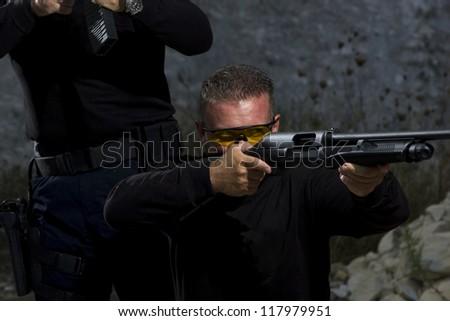 Men shooting on an outdoor shooting range, selective focus - stock photo