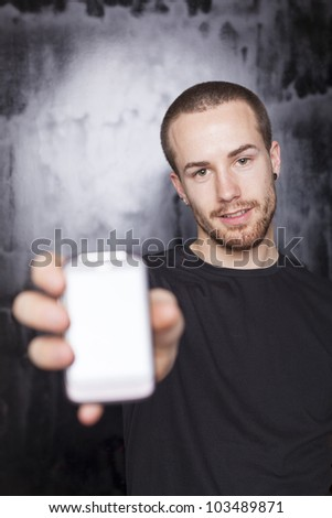 Men showing screen of smartphone, focus on face, black t-shirt and background, studio shot - stock photo
