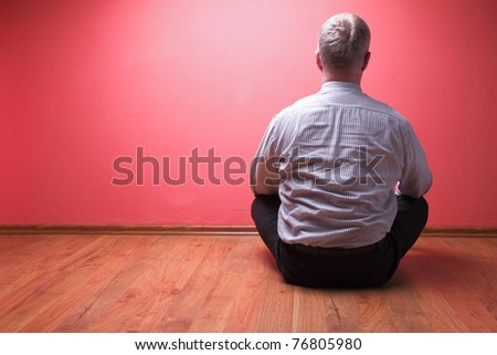 men sited in the floor on red wall background - stock photo