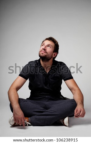 Men sitting and looking up with crossed legs - stock photo