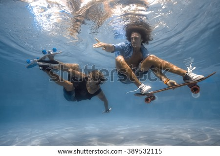 Men skateboarding underwater in the swimming pool