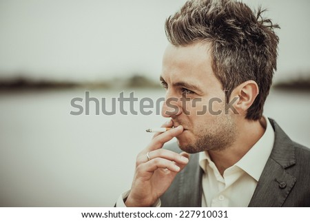 Men smoking sigarette outdoor - stock photo