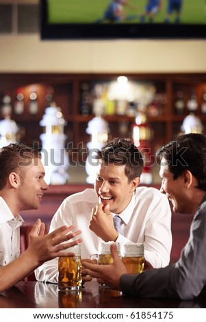 Men speak out for a beer at the bar - stock photo