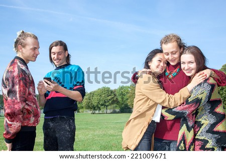 Men stand next group of women hugging each other