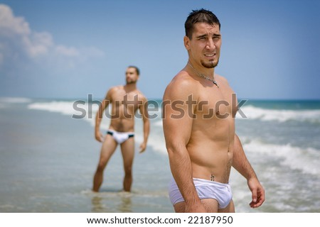 Men standing at the beach - stock photo