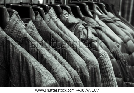 Men sweaters and shirts in different colors on hangers in a retail clothes store - stock photo