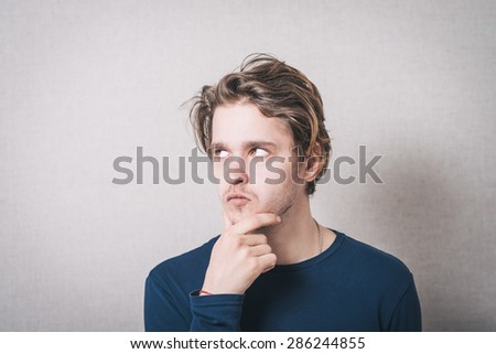 Men think looking to the left. Gray background - stock photo