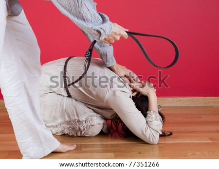 Men threating and beating his wife at home with a belt