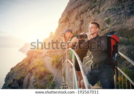Men traveling in the mountains. Guys stand on the bridge and looking through binoculars and photograph nature. - stock photo