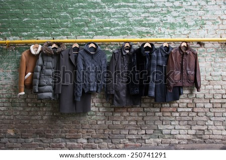 Men trendy clothing on hangers on grunge brick wall. Concept background - stock photo