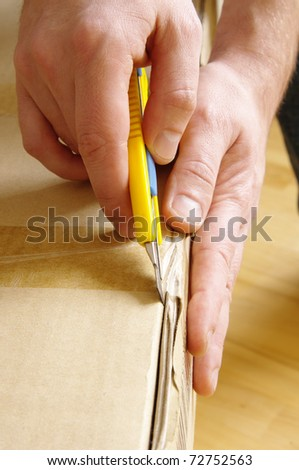Men unpacking box with cutter - stock photo