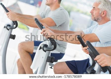 Men using exercise bikes in fitness studio - stock photo