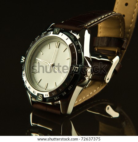 Men watch with a brown leather wristband on a dark glass table - stock photo