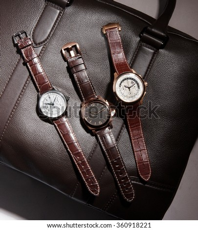 men watches on a close up on a leather bag - stock photo
