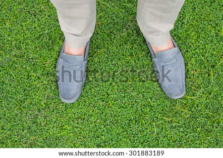 Men wear blue shoes standing on the green grass background.