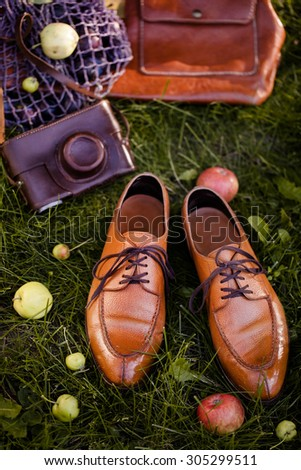 Men wear fashionable shoes standing on the green grass background. male brogue shoes, field enjoying nature summer holidays and vacation concept - stock photo