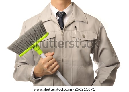 Men wearing work clothes with a cleaning broom