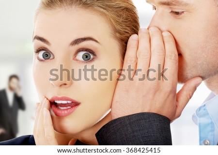 Men whispering secret to his friend - stock photo