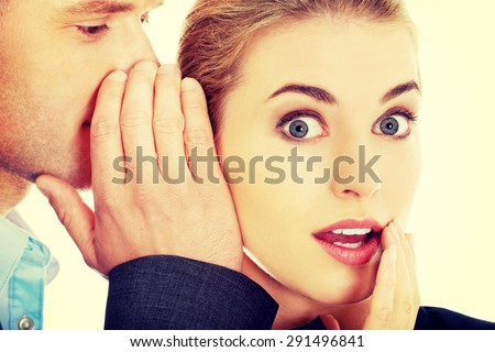 Men whispering secret to his surprised friend - stock photo