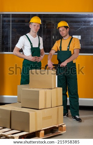 Men with fork pallet truck full of cardboard boxes at warehouse - stock photo