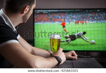 Men with glass of beer watch soccer match in bar. - stock photo