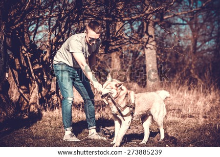 Men with his husky dog playing in the park - stock photo
