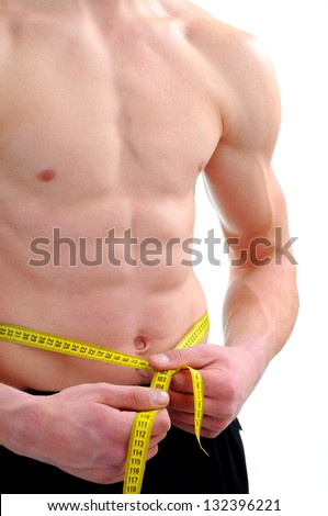 Men with perfect abs measuring his waist - stock photo