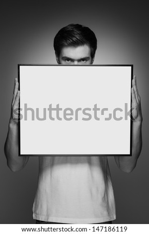 Men with poster. Portrait of young men holding a poster in front of himself while standing isolated on grey - stock photo