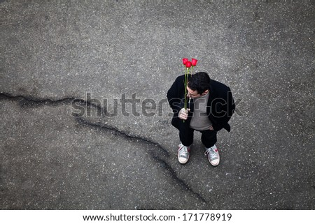 Men with red roses waiting for someone - stock photo