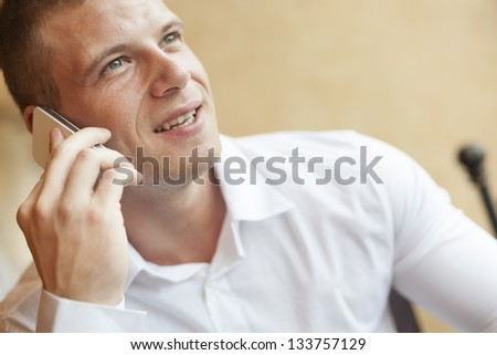 Men with smart phone speaking, blurred background, business building interior