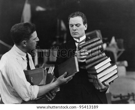 Men with stacks of books - stock photo