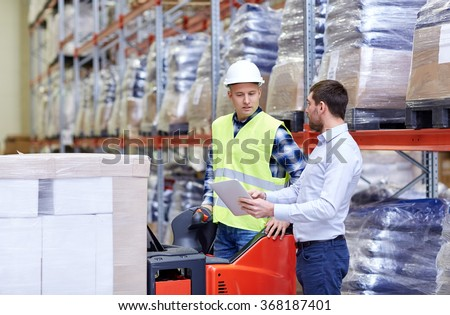 men with tablet pc and forklift at warehouse - stock photo