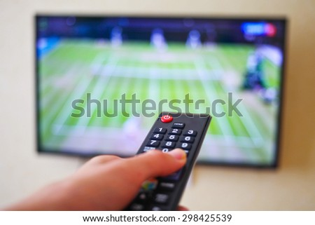 Men with the remote control, front of the television.