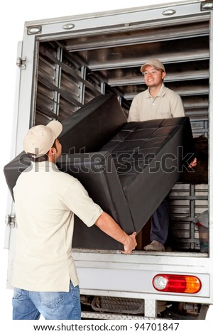 Men working for a moving services company unloading a sofa from a truck - stock photo