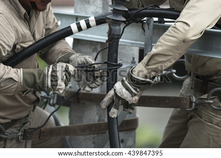men working on a transformer on a electricity power pole - stock photo