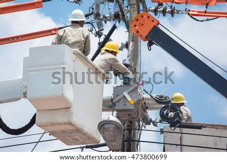 men working on a transformer on a electricity power pole in Thailand