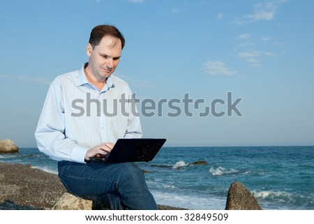 Men working with laptop on the beach