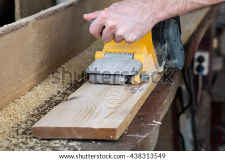 Men working with yellow belt sander on wooden plank in workshop - stock photo