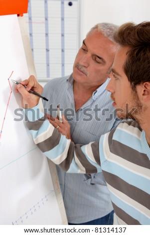 Men writing on a flipboard - stock photo