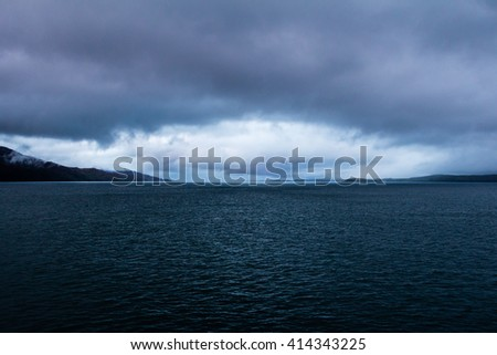 Menacing gathering storm at dusk over an empty sea near Mull, Oban and Lismore, in the Inner Hebrides of Scotland. The all seeing eye of the storm conveys loneliness, and ominous and sullen feelings. - stock photo