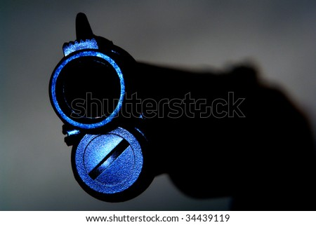 Menacing gun barrel with muzzle nearly facing threatened viewer - stock photo