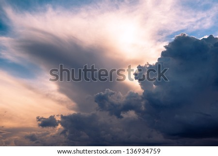 Menacing sky with clouds and sun emerging through translucent clouds - stock photo