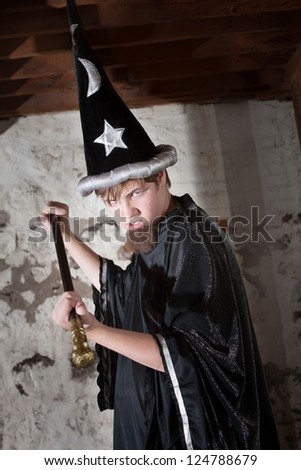 Menacing teenager dressed as wizard with tall hat and scepter - stock photo