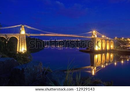 Menai Bridge reflections of the town and Suspension bridge - stock photo